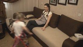 Madre e hija que se derrumban del agotamiento en el sofá en delantales almacen de video