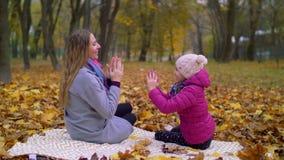 Madre e hija que se divierten en parque del otoño almacen de metraje de vídeo