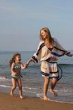 Madre e hija que se ejecutan en las ondas 2 Imagenes de archivo