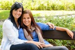 Madre e hija que se relajan en banco de parque Fotos de archivo libres de regalías