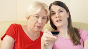 Madre e hija que se relajan en el sofá en casa que ve la TV Canales de la transferencia con teledirigido almacen de video