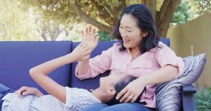 Madre e hija que se relajan en el sofá fuera de 4k casero almacen de video