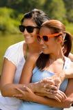 Madre e hija que se relajan en la sonrisa del parque Fotografía de archivo libre de regalías