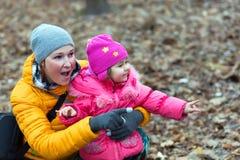 Madre e hija que se sientan en bosque y Live Nature de observación Imágenes de archivo libres de regalías
