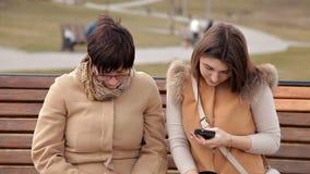 Madre e hija que se sientan en el parque para comunicar y para utilizar un teléfono móvil Naturaleza, relaciones almacen de metraje de vídeo