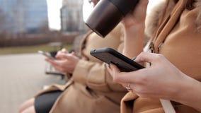 Madre e hija que se sientan en el parque y utilizar el teléfono móvil para escribir los mensajes de SMS almacen de metraje de vídeo