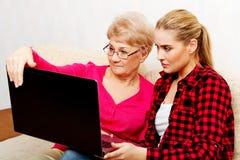 Madre e hija que se sientan en el sofá y que miran algo en el ordenador portátil Imagen de archivo libre de regalías