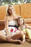Madre e hija que se sientan en Front Of Sofa imagen de archivo libre de regalías