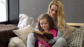 Madre e hija que se sientan en la cama en un abrazo y que leen un libro fotografía de archivo libre de regalías