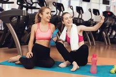 Madre e hija que se sientan en la estera que toma el selfie en el gimnasio Parecen felices, de moda y aptos Imagen de archivo