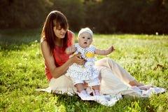 Madre e hija que se sientan en la hierba Fotografía de archivo libre de regalías