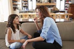 Madre e hija que se sientan en Sofa Laughing Together Imágenes de archivo libres de regalías