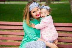 Madre e hija que se sientan en un banco Fotografía de archivo libre de regalías