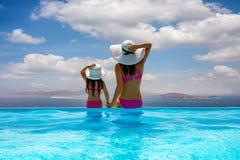 Madre e hija que se sientan en un borde de la piscina y que disfrutan de la visión al mar imágenes de archivo libres de regalías