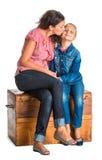 Madre e hija que se sientan en un pecho de madera Imágenes de archivo libres de regalías