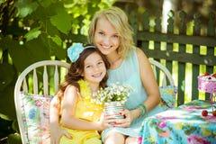 Madre e hija que se sientan en una tabla en jardín Foto de archivo libre de regalías