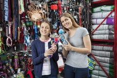 Madre e hija que sostienen los juguetes para el animal doméstico en tienda Imagen de archivo libre de regalías