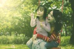 Madre e hija que tienen burbujas de jabón de la diversión que soplan en el parque imagenes de archivo
