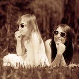 Madre e hija que tienen comida campestre en parque Imagen de archivo