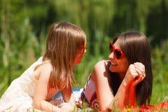 Madre e hija que tienen comida campestre en parque Foto de archivo