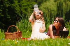 Madre e hija que tienen comida campestre en parque Fotografía de archivo libre de regalías