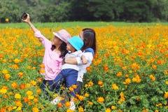 Madre e hija que toman la foto en jardín de flores Fotografía de archivo libre de regalías