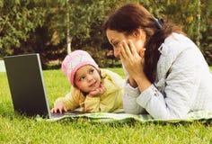 Madre e hija que trabajan en el cuaderno Foto de archivo