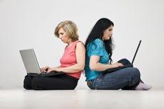 Madre e hija que trabajan en las computadoras portátiles Imágenes de archivo libres de regalías