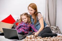Madre e hija que usa el ordenador portátil en cama en dormitorio La madre abraza a su hija con amor y cuidado, y sonríen mientras imagenes de archivo
