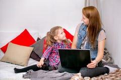 Madre e hija que usa el ordenador portátil en cama en dormitorio Miran uno a y sonríen imagen de archivo libre de regalías
