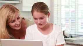 Madre e hija que usa el ordenador portátil junto