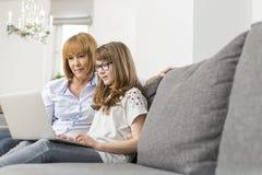 Madre e hija que usa el ordenador portátil junto en casa Foto de archivo