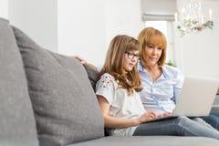 Madre e hija que usa el ordenador portátil junto en casa Fotografía de archivo libre de regalías