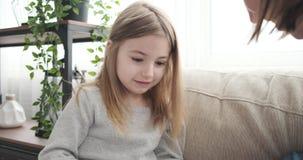 Madre e hija que usa la calculadora en el sof? almacen de video