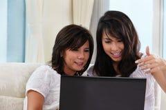 Madre e hija que usa la computadora portátil Fotografía de archivo libre de regalías
