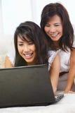 Madre e hija que usa la computadora portátil Imagen de archivo libre de regalías