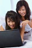 Madre e hija que usa la computadora portátil Foto de archivo