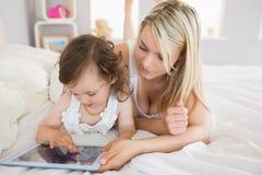Madre e hija que usa la tableta digital en cama imagen de archivo libre de regalías