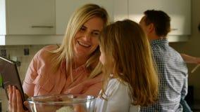 Madre e hija que usa la tableta digital mientras que prepara la comida metrajes