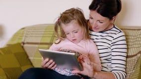Madre e hija que usa la tableta en el sofá almacen de video