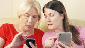 Madre e hija que usa smartphones, hojeando, leyendo noticias Soledad en concepto de la era de la tecnología metrajes