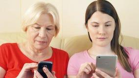 Madre e hija que usa smartphones, hojeando, leyendo noticias Soledad en concepto de la era de la tecnología almacen de video