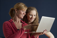 Madre e hija que usa un ordenador portátil Imagen de archivo libre de regalías