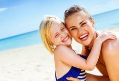 Madre e hija sanas sonrientes en el abarcamiento de la costa Imagen de archivo
