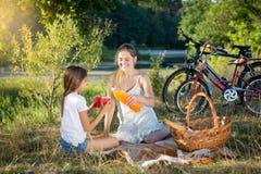 Madre e hija sonrientes que beben el zumo de naranja en la comida campestre Imágenes de archivo libres de regalías