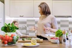 Madre e hija sonrientes que cocinan junto en la ensalada vegetal de la cocina Comida, padre de la comunicaci?n y ni?o caseros san foto de archivo