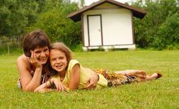 Madre e hija sonrientes que mienten en césped verde imagenes de archivo