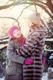 Madre e hija sonrientes que se divierten en día de invierno frío Fotografía de archivo