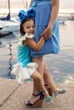 Madre e hija tres años en un arco grande del vestido azul Imagen de archivo