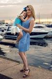 Madre e hija tres años en un arco grande del vestido azul Fotos de archivo